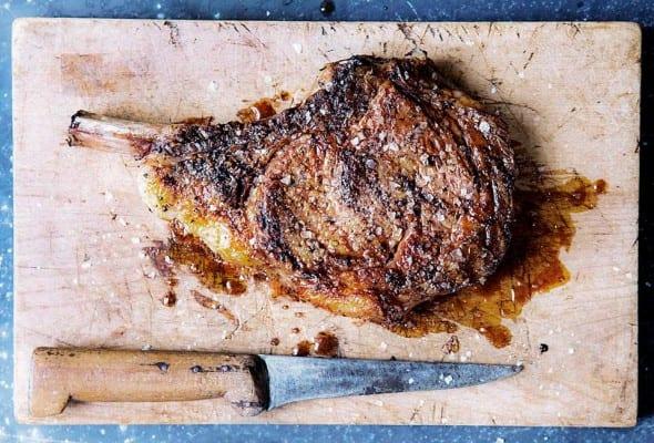 Cutting board and knife with a salt and pepper rib eye steak