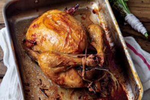 A perfect roast chicken in a metal roasting pan that is resting on a kitchen towel, with a bunch of herbs beside it.
