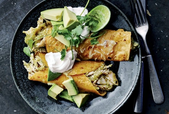 Two chicken enchiladas with green sauce in a black shallow bowl with cubed avocado, sour cream, cilantro, and a lime half.