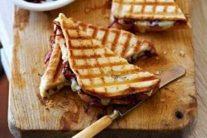 Two halved grilled cheese with onion jam on a wooden cutting board alongside a dish of onion jam and a butter knife.