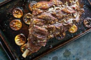 A whole roast leg of lamb on a rimmed baking sheet with charred lemon slices surrounding the lamb.