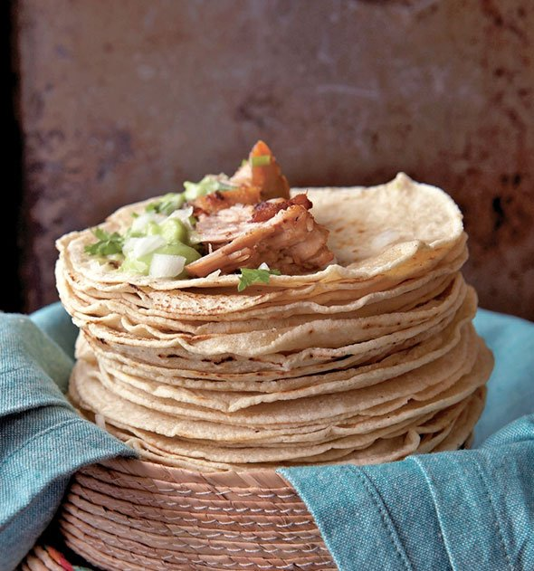 A stack of flour tortillas topped with pork for carnitas tacos.