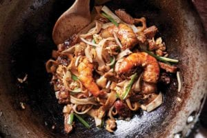 A metal wok with a serving of char kway teow and a wooden spoon resting inside.