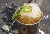A jalapeno mint julep in a pewter julep cup, topped with a mint sprig and jalapeno slice.
