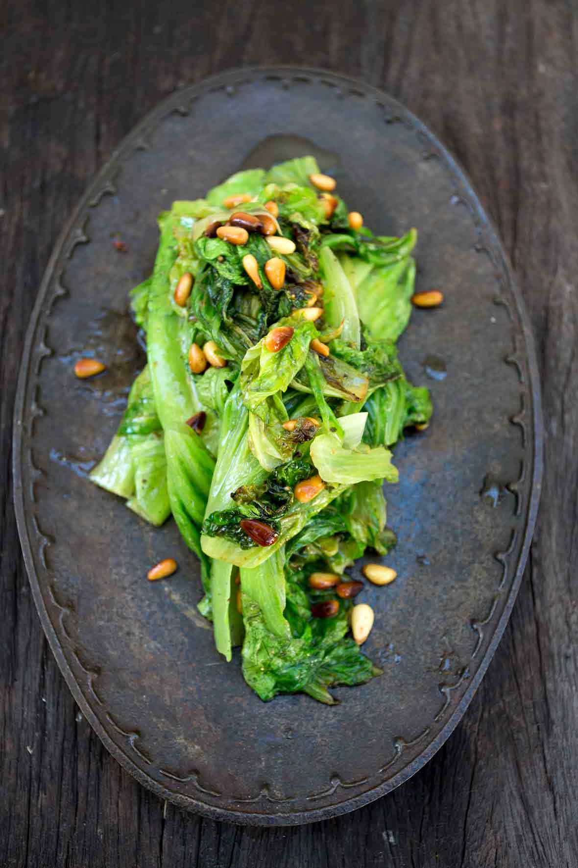 An iron plate with a pile of sautéed romaine lettuce topped with toasted pine nuts