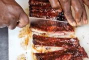 A person cutting a slab of best St. Louis ribs on a white cutting board.