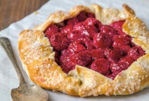 A raspberry crostata--a rustic tart with the crust folded over a filling of raspberries--on a sheet of parchment
