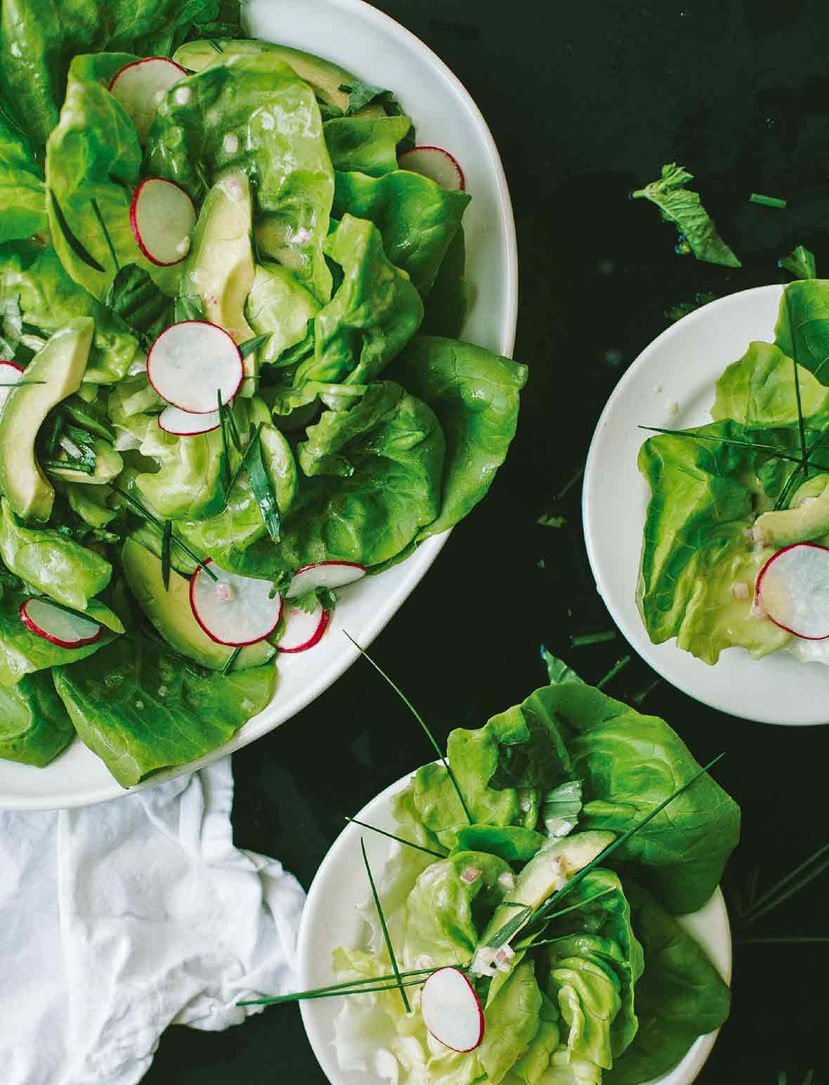 Spring salad with creamy shallot vinaigrette with sliced radishes, avocados, and chives on three plates