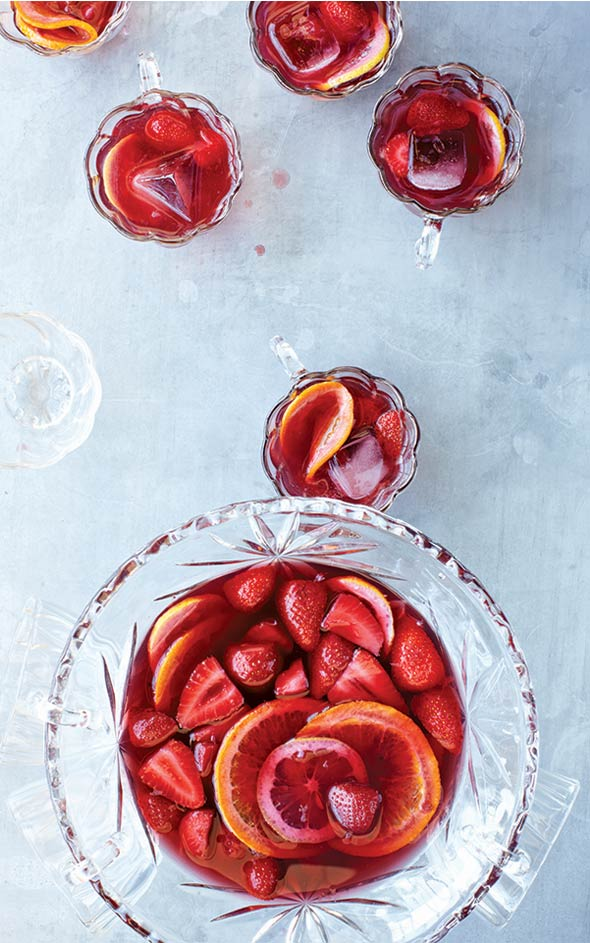 A punch bowl and several glasses filled with strawberry sangria, whole strawberries, and orange wheels.