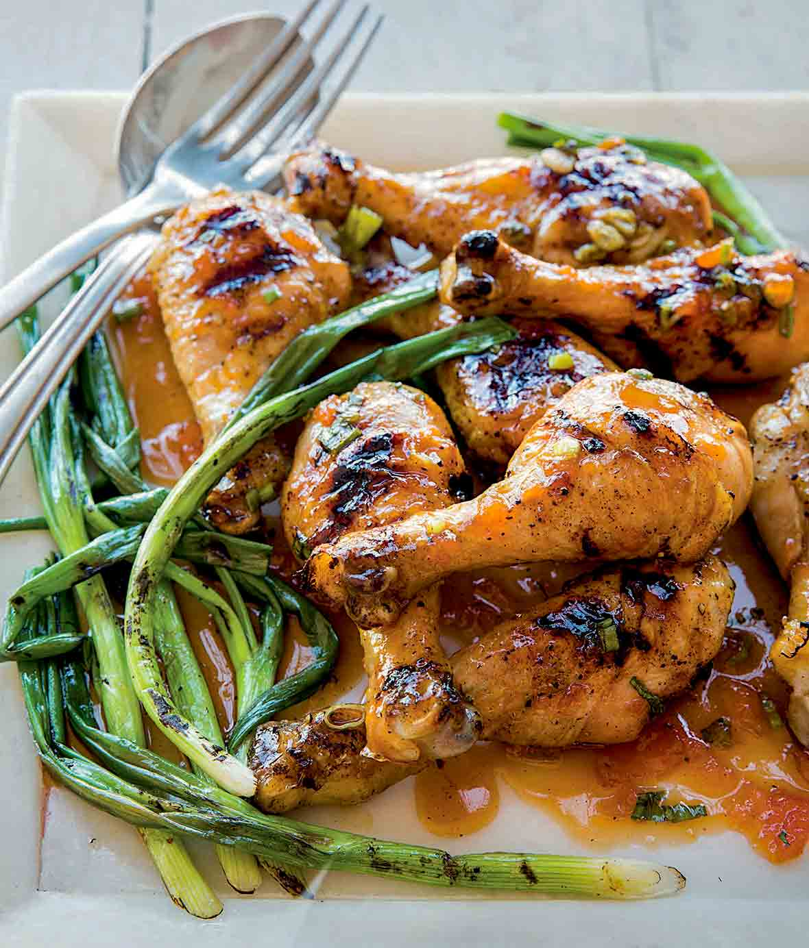 Square plate of a pile of grilled sweet and sticky sriracha drumsticks and grilled scallions