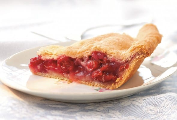A slice of sour cherry pie on a white plate.
