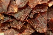 A pile of pieces of Sriracha beef jerky.
