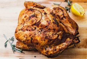 Whole roast chicken with browned lemon slices on the skin all on a cutting board