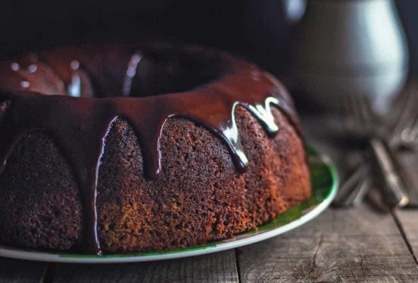 A chocolate zucchini cake glazed with chocolate icing on a green plate on a wooden table