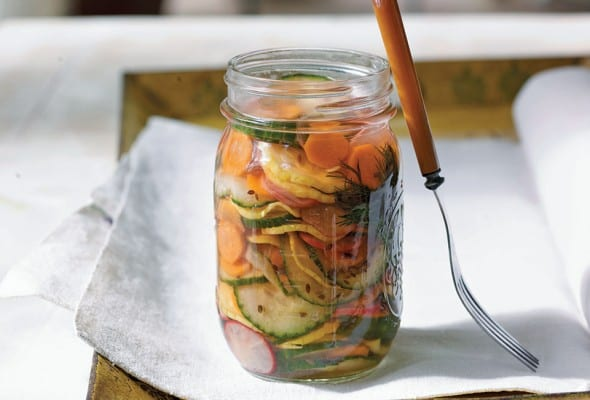 A jar of confetti quick pickles on a white napkin with a fork resting against the jar.