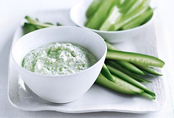 A white platter with sliced celery and cucumber and a white bowl of feta dip on top.