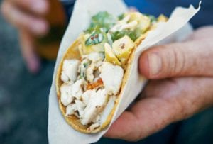 A hand holding a grilled fish taco topped with cilantro that is wrapped in a paper napkin.