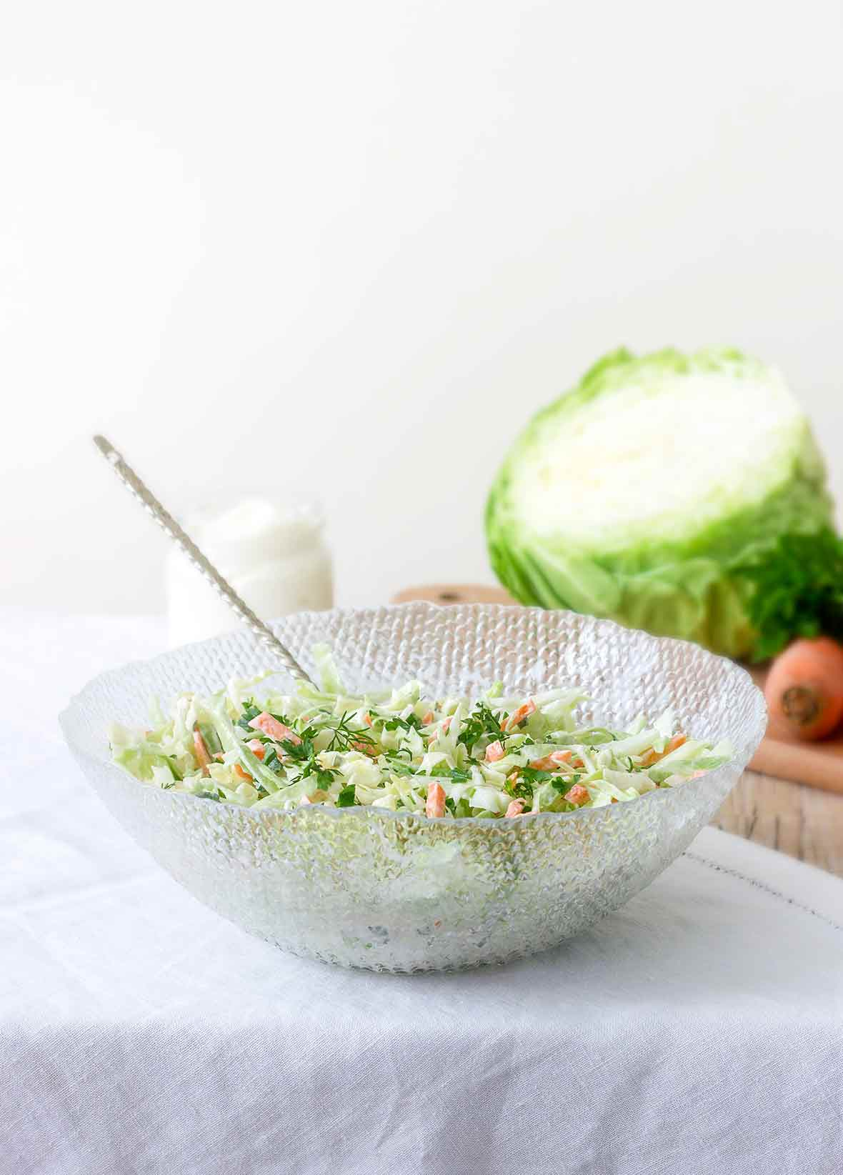 Glass bowl with lime coleslaw--green cabbage, carrots, lime zest, mayo, and parsley--on a tablecloth, cabbage and carrots behind