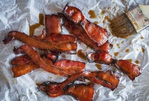 Several strips of maple bacon on a sheet of parchment, with a pastry brush and drizzles of maple syrup beside the bacon.