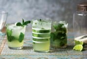 Three glasses of classic mojito, with two lime wedges and a jar of sugar beside them.