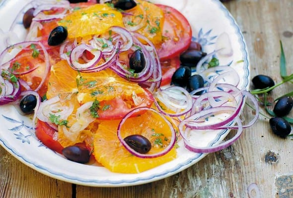 A patterned plate topped with a Moroccan salad made with sliced oranges and tomatoes, black olives, and sliced red onion.