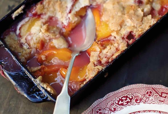 A spoon resting in a glass baking dish of peach cobbler, plus a helping of peach cobbler on a decorative plate.