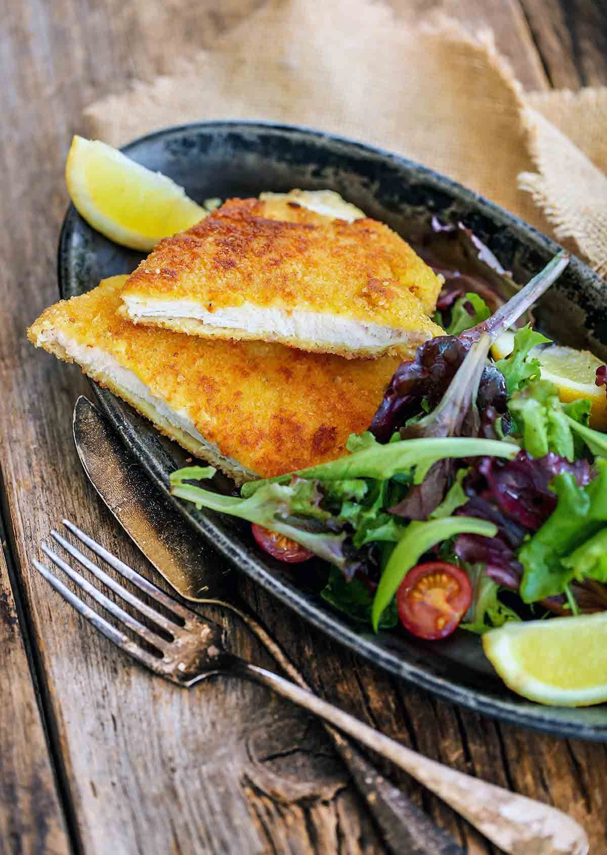 A halved pork Milanese cutlet on a grey oval plate with a lemon wedge and mixed spring greens.