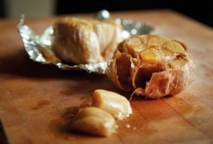 Two heads of roasted garlic--one in foil, one unwrapped--drizzled with oil on a cutting board