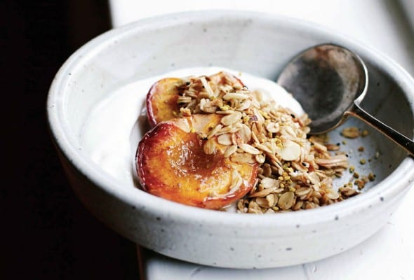 A white bowl of roast peaches topped with an easy granola of oats and almonds, Greek yogurt underneath