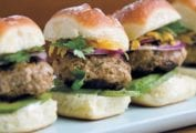 Three small turkey burgers with onions, parsley, avocado on a white plate