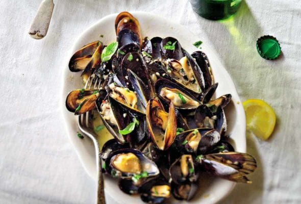 White plate with steamed mussels in beer, topped with parsley, nearby lemon wedges and a bottle of beer