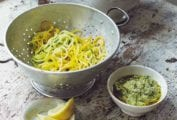A wooden table with a colander holding veggie spaghetti, a small white bowl of pesto, and a small dish of lemon wedges.