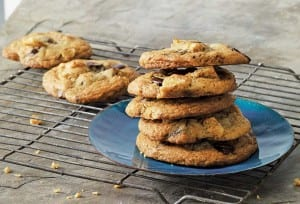 A stack of chicharron chocolate chip cookies on a blue plate on a wire rack with a couple more cookies on the rack.