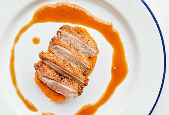 A sliced duck breast with maple bourbon sauce drizzled around it on a blue-rimmed white plate.