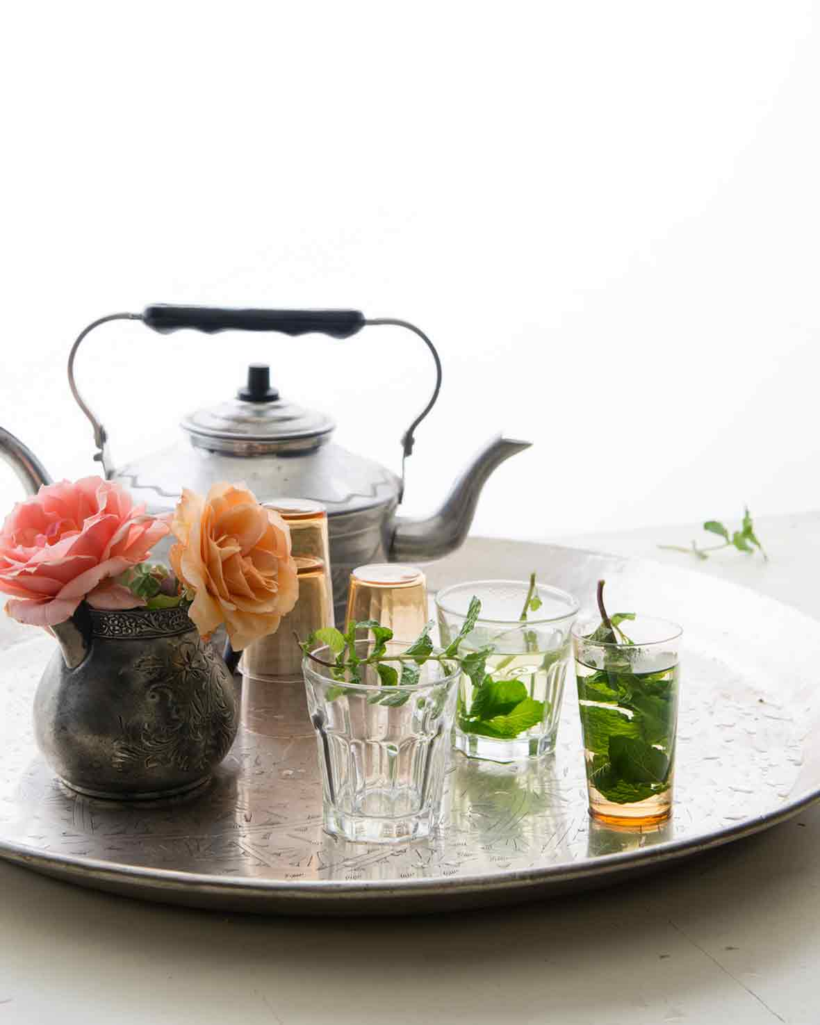 A teapot, a collection of glasses, three partially filled with mint tea, and a vase of flowers on a silver tray.