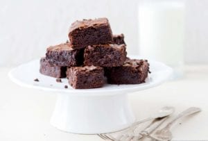 A white cake stand of a pile of one-pot cocoa brownies, a glass of milk, on a white table