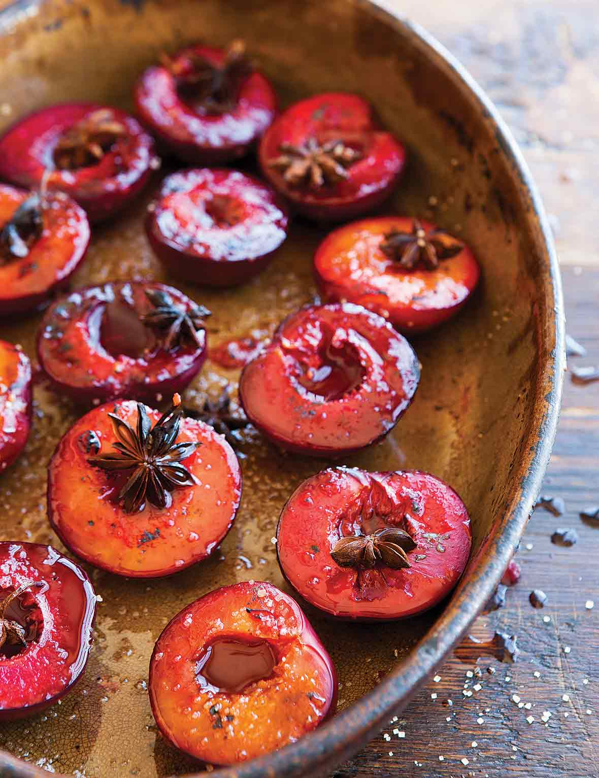 An oval dish filled with roasted plums, topped with star anise.