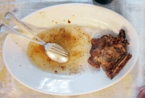 Oval plate with a salt and pepper pork chop, spoon, fork, and juice on it