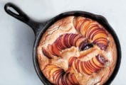 A cast-iron skillet with a golden cake with slices of fanned out plums baked in