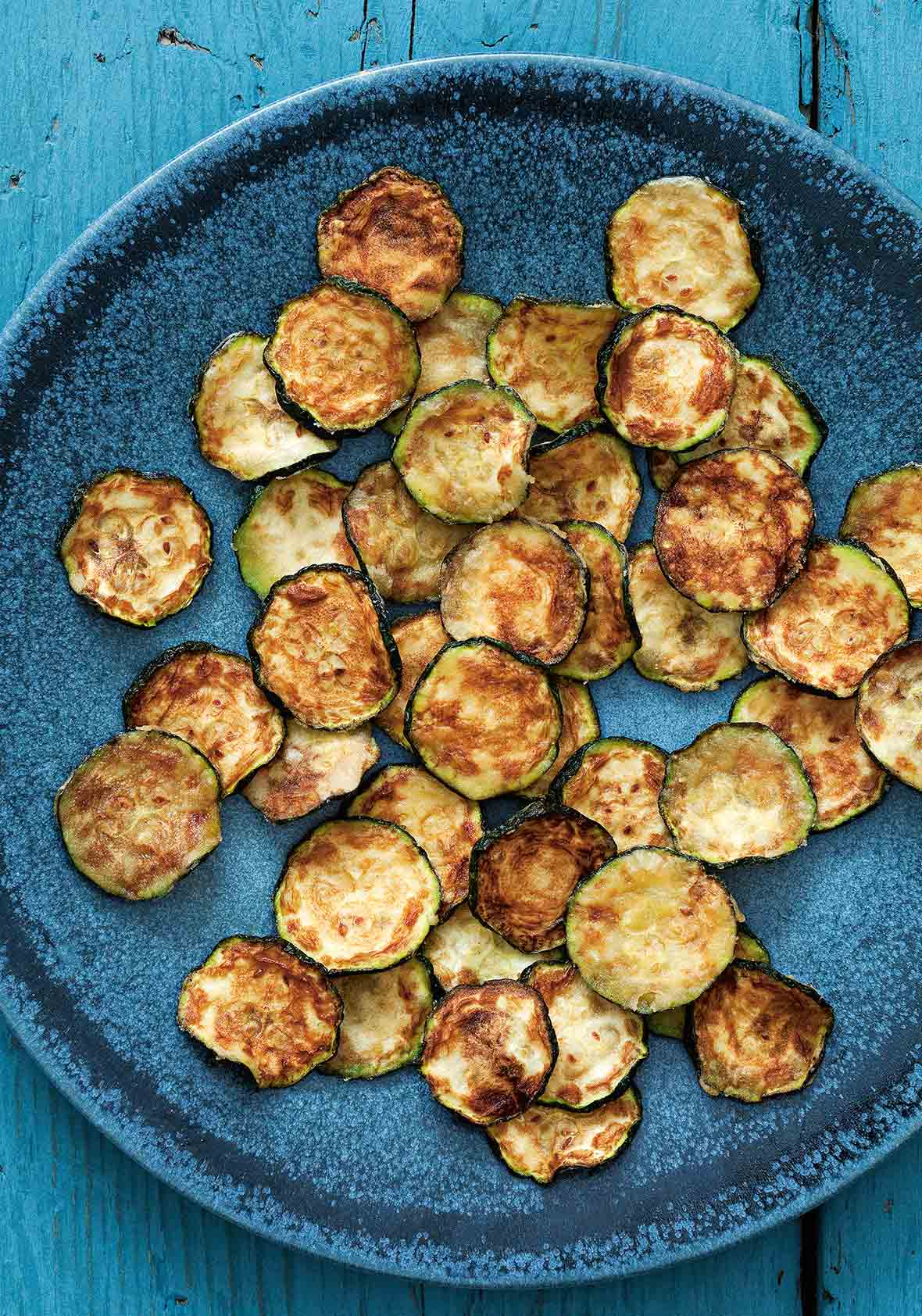 A blue plate filled with slices of zucchini crisps.
