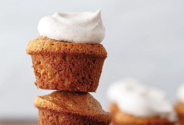 A stack of three banana bread muffins, with the top one topped with chai whipped cream.