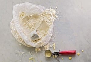 An open plastic bag of homemade pancake mix with a mug for scooping and an ice cream scoop on the side for the batter.