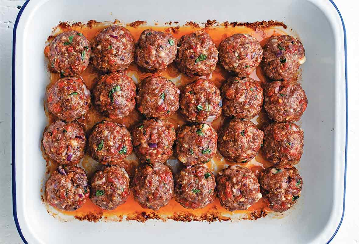 White pan of 24 orange-red chorizo golf-ball-size meatballs