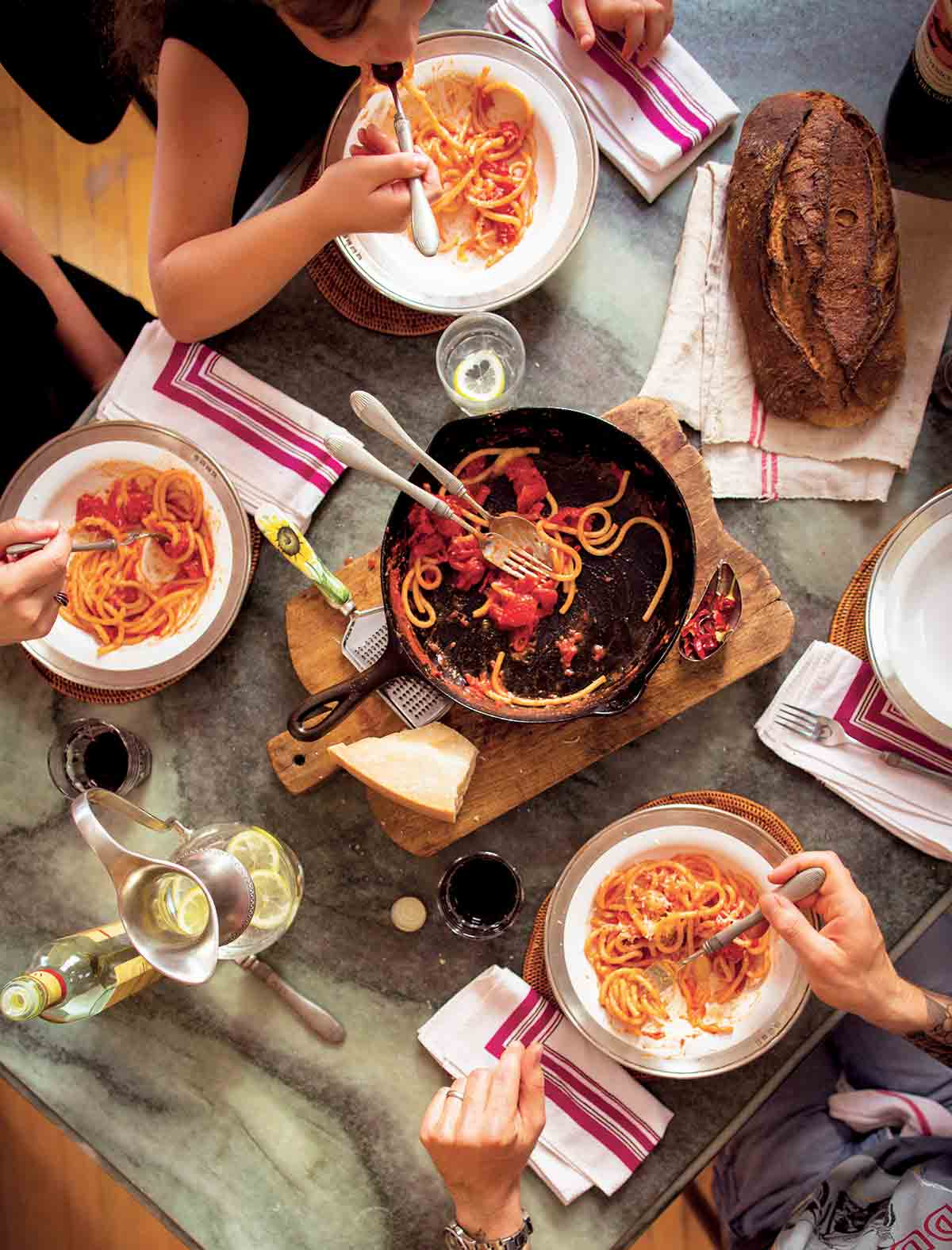 People gathered around a cast-iron skillet on a wooden board with some spaghetti and red sauce.