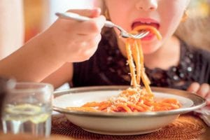 A child eating a bowl of cooked pasta with red sauce.