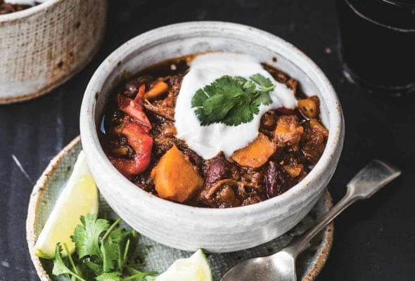 A bowl of shredded beef chili with sweet potatoes on a plate containing a spoon, two lime wedges, and cilantro leaves.