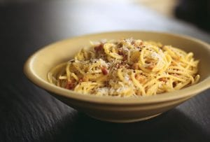 A bowl filled with spaghetti carbonara, topped with freshly grated Parmesan.