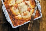 A blue and white square baking dish filled with vegetable lasagna that has been cut into 9 squares with a knife resting on top.