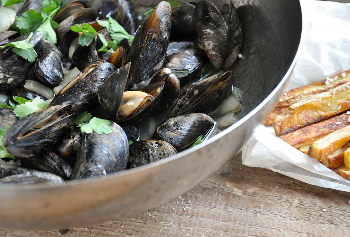 A bowl of apple cider steamed mussels topped with parsley, fries on the side
