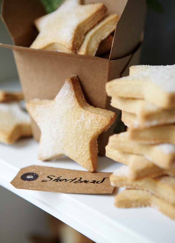 A stack of star-shaped cutout classic shortbread cookies, lightly dusted with sugar, and a brown takeout container and a gift tag